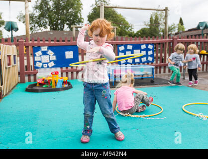 Nursery school children playing in a playground in Warwickshire, UK - Stock Photo