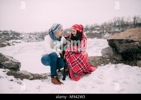 Young couple in hats and scarfs with dog wrapped in red plaid during winter walk next to frozen lake and rocks. - Stock Photo
