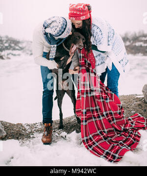 Young couple in hats and scarfs wrapped in red plaid are standing and kissing of dog next to frozen lake and rocks during winter walk. - Stock Photo