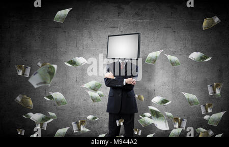 Businessman in suit with TV instead of head keeping arms crossed while standing among flying euros and with gray dark wall on background. - Stock Photo