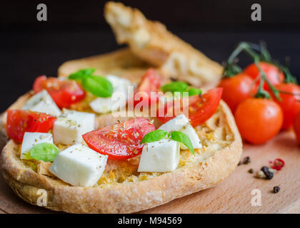 Italian starter friselle. Classical frisella tomato, cheese mozzarella and basil with oregano and olive oil. Dried bread called freselle on wooden boa - Stock Photo