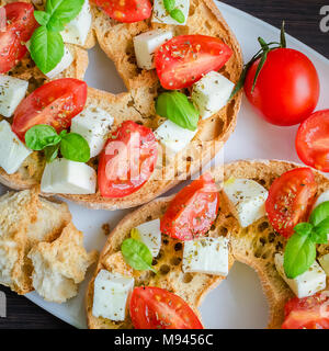 Italian starter friselle. Classical frisella tomato, cheese mozzarella and basil with oregano and olive oil. Dried bread called freselle on white plat - Stock Photo