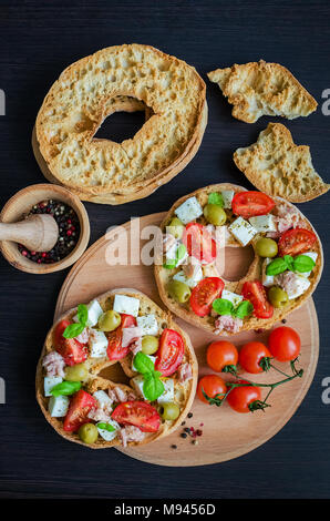 Classical frisella tomato, cheese mozzarella, tuna and olives. Italian starter friselle. Dried bread called freselle on wooden board with tomatoes che - Stock Photo
