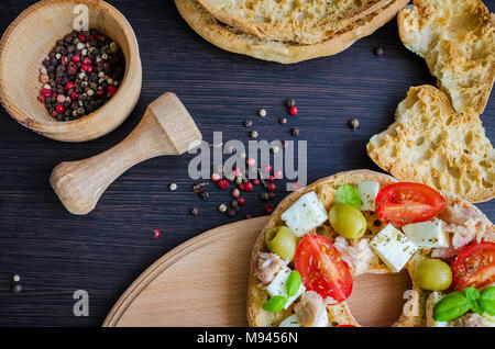 Italian appetizer Friselle. Italian dried bread Friselle with tomatoes cherry, cheese mozzarella, olives, tuna, basil and pepper in wooden pounder. It - Stock Photo