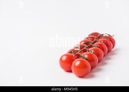 raw cherry tomatoes laying on white background - Stock Photo