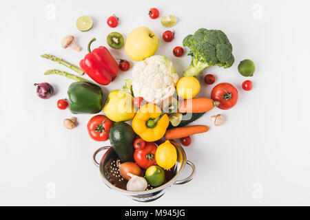 Flat lay composition of colorful vegetables and fruits in colander isolated on white background - Stock Photo