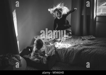 Girl jumping on bed with baby next to her - Stock Photo