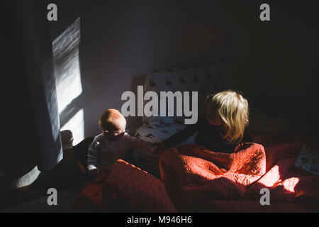 Girl and baby holding each other in separate beds - Stock Photo