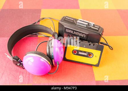 Walkman, cassette tape and headphones on a colorful checkered tablecloth. - Stock Photo