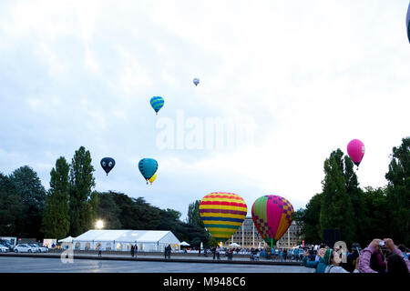 Colourful Hot air Balloons lifting off into clouds over a white marquee, taking part in Hot Air Ballooning Festival in Canberra - Stock Photo
