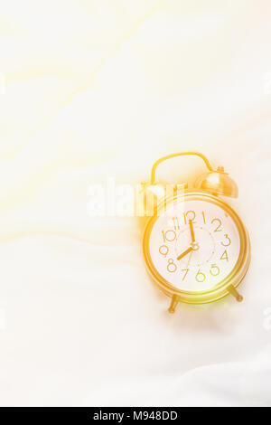 Alarm Clock Showing Eight O'Clock Lying on White Bed Blanket in Bedroom. Bright Golden Morning Sunlight Streaming Through Window. New Day Beginning Wa - Stock Photo