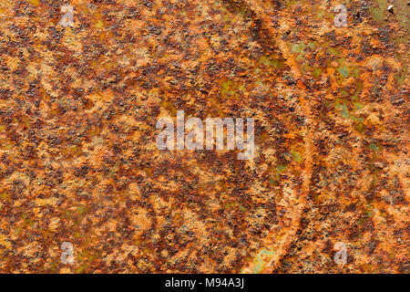 Rust is eating the metal of a tin can top creating multiple colors and textures - Stock Photo