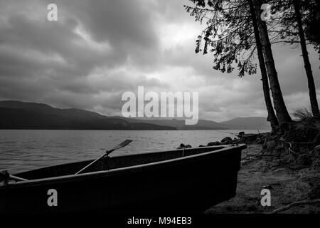 Small fishing boat silhouette at the shore with partial pines in cloudy dark rainy morning at lake Dospat, Rhodope mountain, Bulgaria - Stock Photo