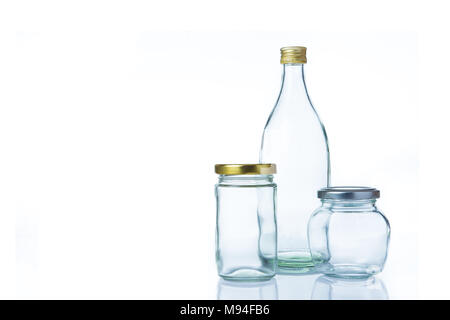 Empty clear glass bottles in various sizes and shapes with lids on white background - Stock Photo
