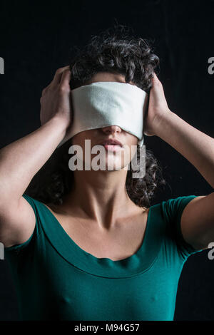 Portrait of a blindfolded woman with dark hair - Stock Photo