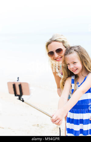 beautiful mother and her cute daughter doing a selfie photo with her phone on a beach in thailand - Stock Photo