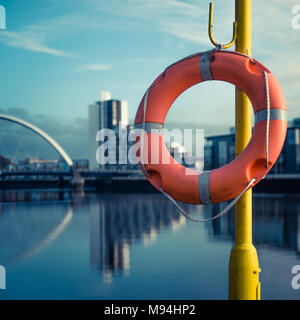 Orange Life Buoy With River Clyde and Arc Bridge in the Background - Stock Photo