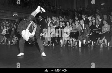 High schoolers demonstrate the Jitterbug dance to a crowd in a hotel ballroom in Chicago in 1958. - Stock Photo
