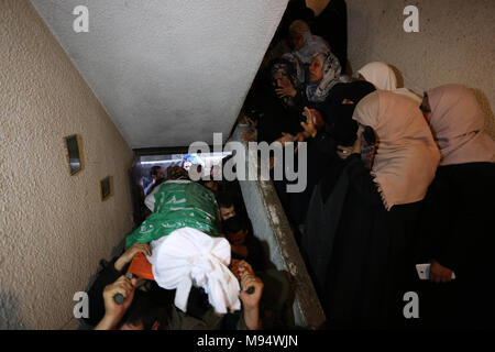 Nuseirat, Gaza Strip, Palestinian Territory. 22nd Mar, 2018. Relatives of Palestinian Ziyad Al-hawajri, react as mourners carry his body out of the family house during his funeral in Nuseirat, central Gaza Strip, Thursday, March 22, 2018. Al-hawajri, is one of the two members of Hamas security forces who were killed Thursday during an operation to arrest suspects wanted for a bombing that targeted the visiting Palestinian premier's convoy in Gaza last week Credit: Ashraf Amra/APA Images/ZUMA Wire/Alamy Live News - Stock Photo