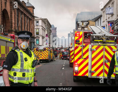 Hope Street, Glasgow, Scotland, United Kingdom, 22nd March 2018. A major fire involving multiple buildings closes streets in central Glasgow. Fire engines attend the incident. A policeman wears a mask due to the risk of asbestos from the smoke - Stock Photo