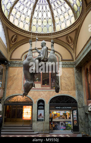 In the marbled atrium where the tickets can be bought for the cinema, hangs David Cerny's sculpture called Kun, an equestrian sculpture of  St Wenceslas in Wenceslas Square in Lucerna Gallery, on 19th March, 2018, in Prague, the Czech Republic. Lucerna is the most elegant of Nove Mesto's many shopping arcades runs through the art-nouveau Lucerna Palace (1920), between Stepanska and Vodickova streets. The complex was designed by Vaclav Havel (grandfather of the former president), and is still partially owned by the family. It includes theatres, a cinema, shops, a rock club and several cafes and - Stock Photo