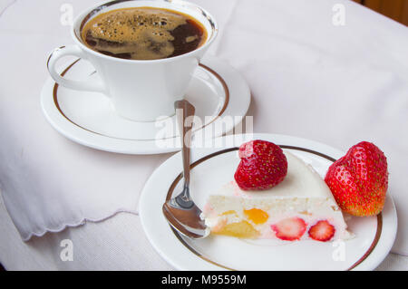 a piece of strawberry dessert on a white plate with a Cup of coffee - Stock Photo