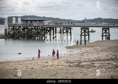 Beaumaris beach and pier with people enjoying afternoon spend outdoor.Beaumaris,Anglesey,United Kingdom,21 April,2017. - Stock Photo
