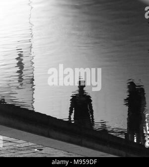Reflections of two people on the rippled surface of a canal in the city of Milan, Italy - Stock Photo