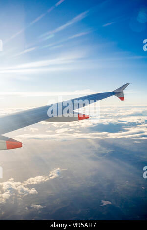 View from an airplane window in mid flight to the airplane wing with blue sky and stratocumulus clouds visible - Stock Photo