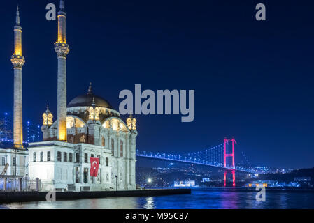 Exterior view of Ortakoy Mosque with15 July Martyrs Bridge or unofficially Bosphorus Bridge also called First Bridge over bosphorus in Istanbul,Turkey - Stock Photo