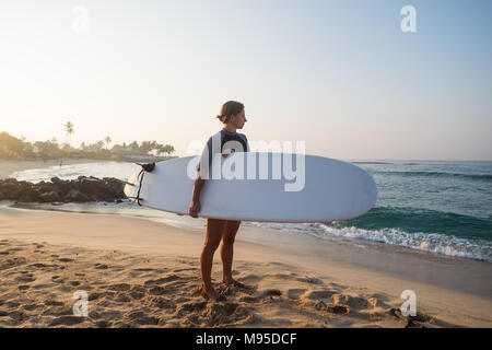 caucasian woman with surfboard standing near water and looking at waves. ready to start surfing - Stock Photo