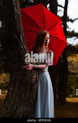 Mary Poppins, modern fashion concept. Caucasian white female model standing with red umbrella and enjoying weather. Beautiful woman with long hair, in - Stock Photo