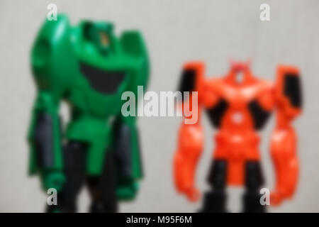 Blur image of green and orange robots on grey background. - Stock Photo