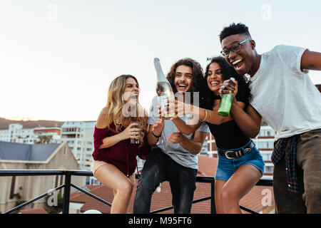 Outdoor shot of young woman opening a bottle of champagne with friends. Young people having champagne at rooftop party. - Stock Photo