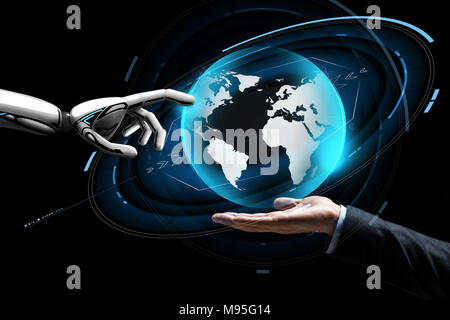 human and robot hand with virtual earth hologram - Stock Photo