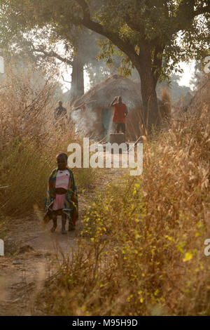 Little girl stands on a path other people at the background in the early morning light - Stock Photo