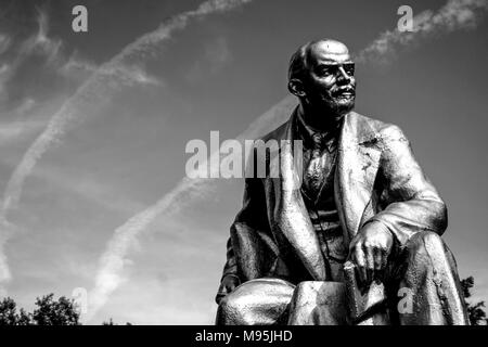 A black and white image of a statue Lenin in a square near St Petersburg, with contrails from aircraft in the sky. - Stock Photo