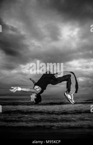 A monochrome, action shot of a man flipping on a beach. - Stock Photo