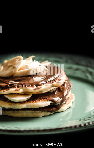 American pancakes with chocolate and banana on a pastel green rustic with black background plate - Stock Photo