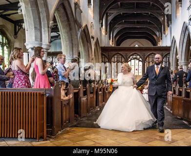 Bride and groom walking down aisle after getting married - Stock Photo