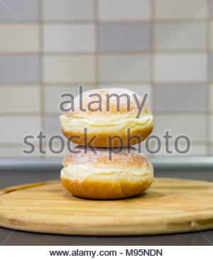 Two fresh sugar doughnuts on a wooden board in soft focus - Stock Photo