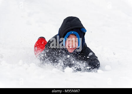 A little boy (5 yr old) grimacing as snow goes into his face as he slides face first in the snow - Stock Photo