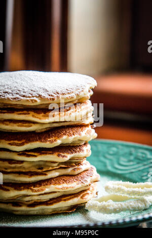 American pancakes with sugar on a pastel green rustic plate - Stock Photo