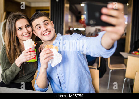 Happy couple eating burger and doner taking selfie together in fast food - Stock Photo