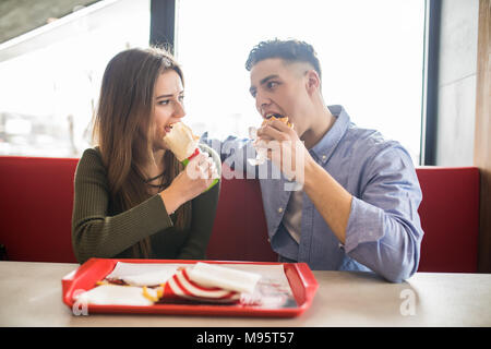 Happy couple eating fast food burger and doner in fast food cafe - Stock Photo