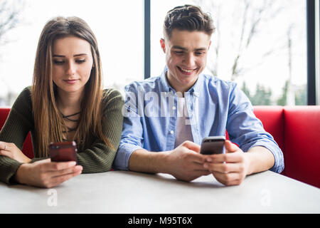phubbing, always connected, internet addiction, young couple in cafe looking at their smartphones, social network concept - Stock Photo