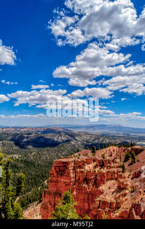 Scenic overlook with red and orange sandstone cliffs, and green valley below under a bright blue sky with white fluffy clouds. - Stock Photo