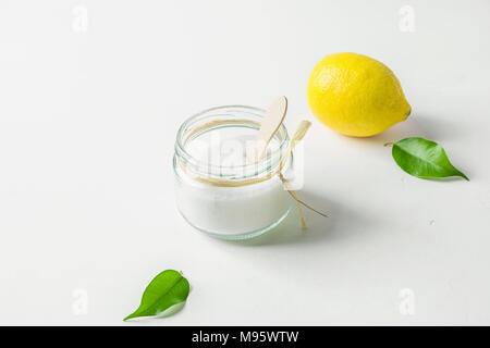 Ripe Yellow Lemon Green Citrus Leaves Sugar in Glass Jar. Ingredients for Face Scrub on White Concrete Stone Tabletop. Wellness Organic Cosmetics Ayur - Stock Photo