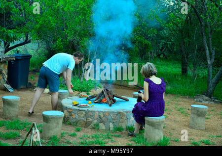South Africa is a popular tourist destination for its blend of true African and European experiences. Campers enjoying barbecue in private reserve.. - Stock Photo