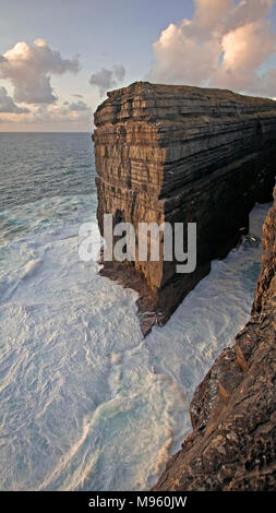 Waves crashing against cliffs at Loop Head on Ireland's Atlantic west coast in County Clare - Stock Photo